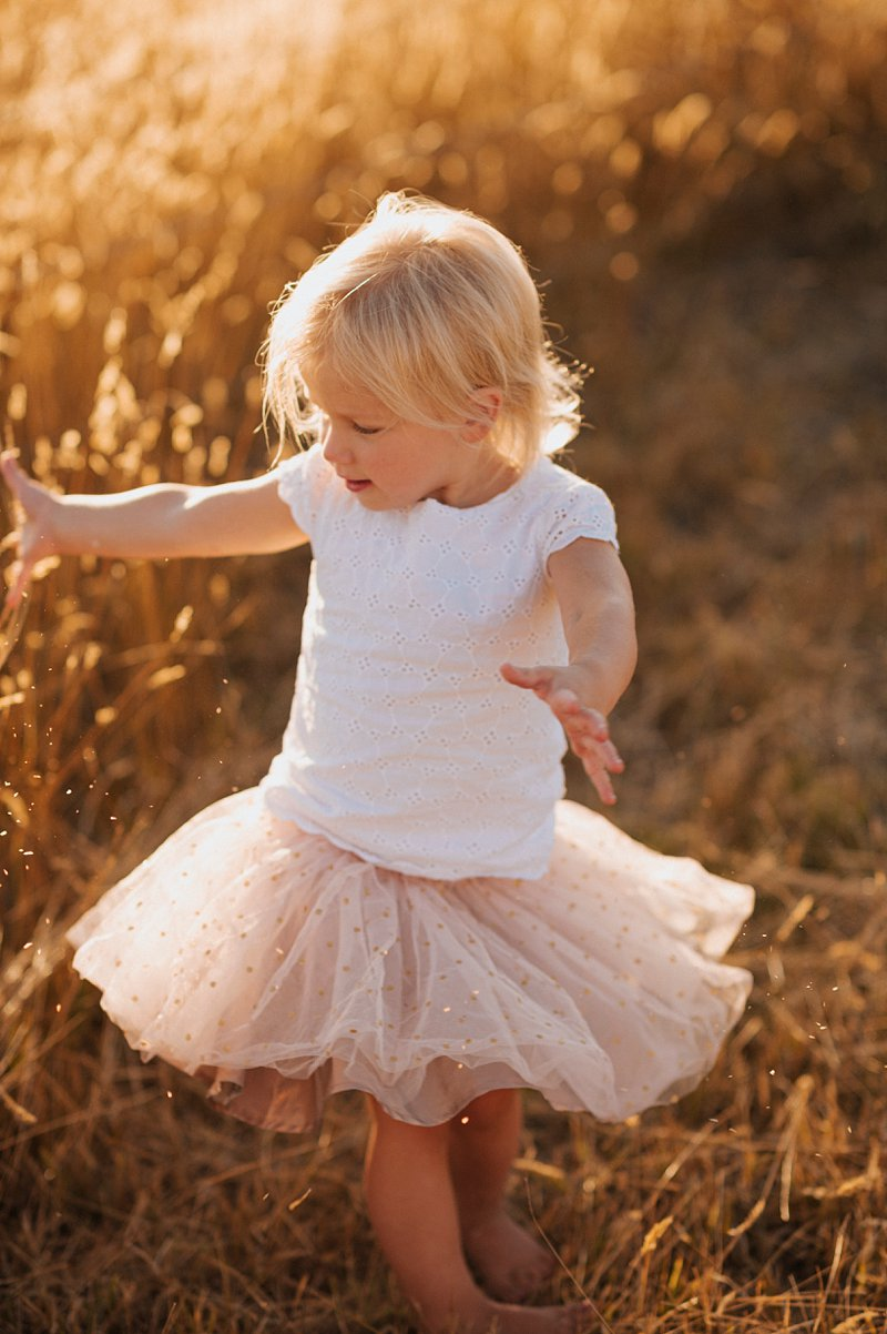 little girl dancing in field, sunkissed blonde girl, family portraits at sunset