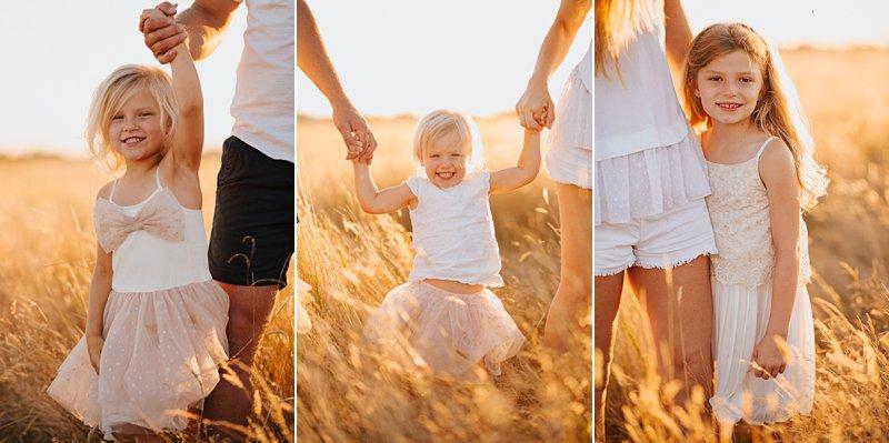 little girls holding parents hands, walking portrait of children family portraits at sunset